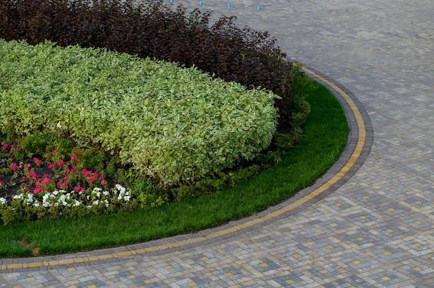 Straat met bloemen en wandelpad in het park geplaveid met stenen tegels