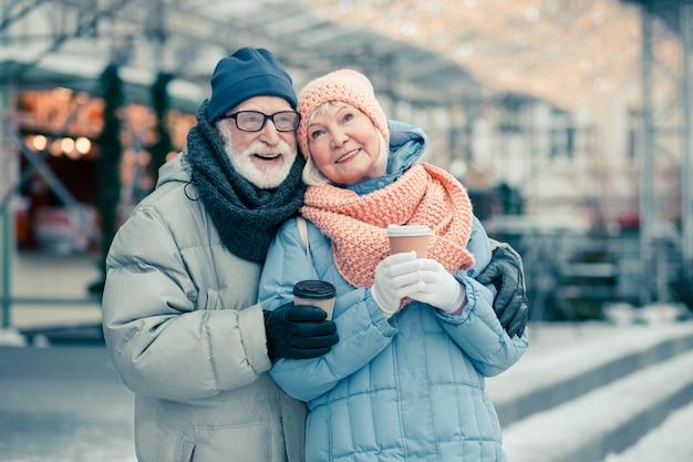 Straat met kerstverlichting op de achtergrond. bejaard echtpaar glimlachend terwijl ze knuffelen en kartonnen kopjes koffie vasthouden