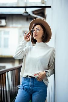 Straat mode geïnteresseerde vrouw met hoed, spijkerbroek, brede hoed en transparante bril op balkon
