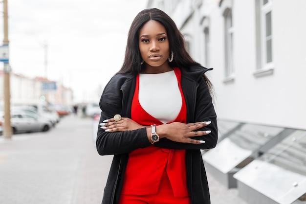 Straat portret mooie jonge afrikaanse vrouw met lang haar met schone huid met sexy lippen in stijlvolle elegante kleding buiten in de buurt van vintage gebouw. aantrekkelijke zwarte meid in trendy outfit in de stad.