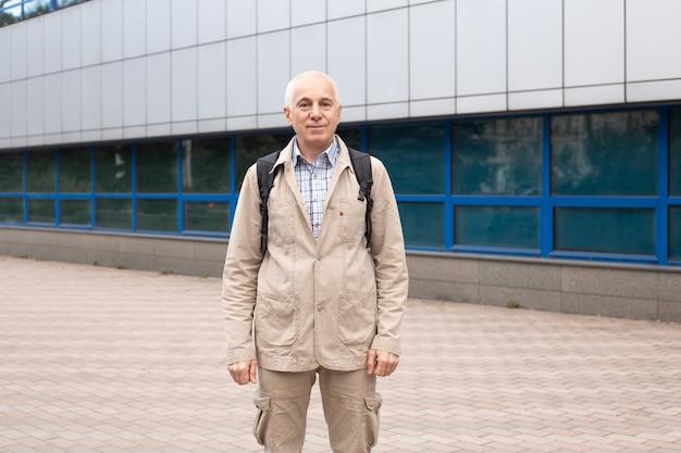 Straat portret van volwassen man in casual outfit staande op straat in de stad