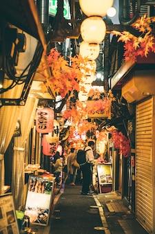 Straat 's nachts in de stad met lichten en mensen