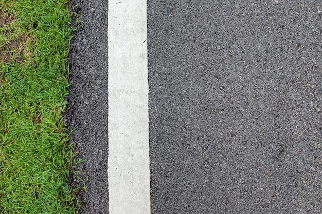 Straat van het oppervlakte grunge de ruwe asfalt zwarte donkergrijze weg en groene grastextuur