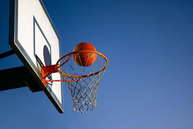 Straatbasketbalbal die in de hoepel buiten valt.