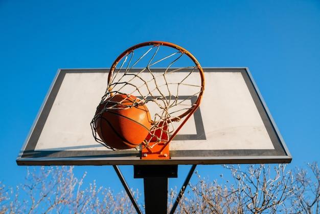 Straatbasketbalbal die in de hoepel valt, stedelijk jeugdspel.