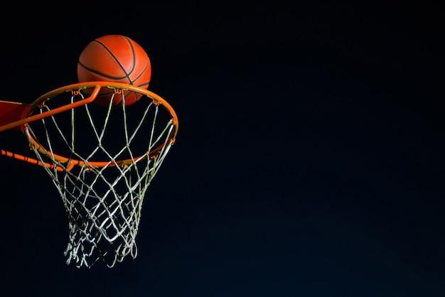 Straatbasketbalbal die 's nachts in de hoepel valt, stedelijk jeugdspel.