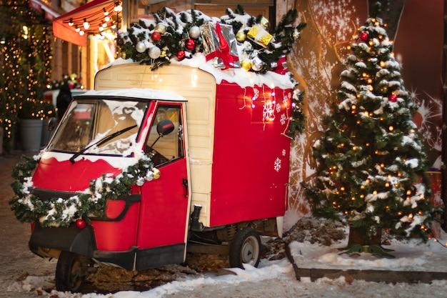 Straatdecoratie met kleine rode retro scooter en een kerstboom