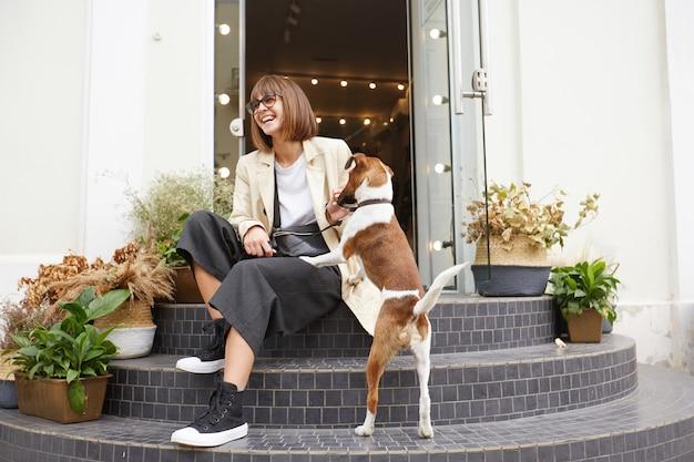 Straatfoto van aantrekkelijke vrouw zittend op de trap, vlakbij is haar mooie hond jack russell terrier
