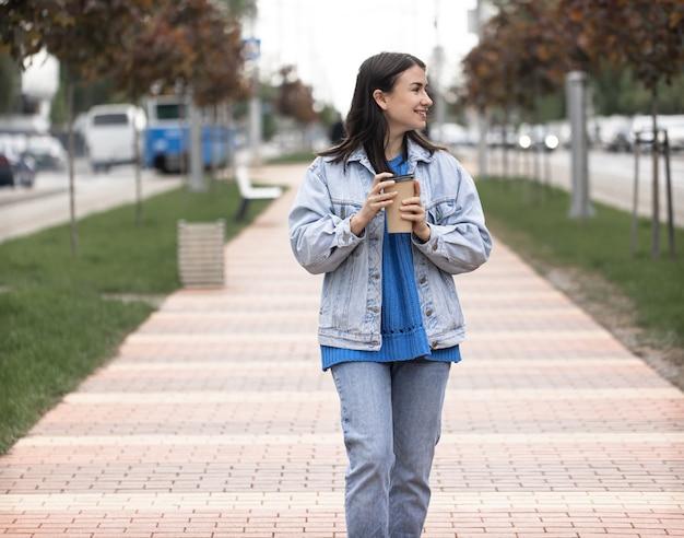 Straatfoto van een aantrekkelijke jonge vrouw die door een stadsstraat loopt met een kopje koffie in haar hand