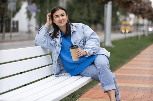 Straatfoto van een aantrekkelijke jonge vrouw zittend op een bankje met een kopje koffie in haar hand