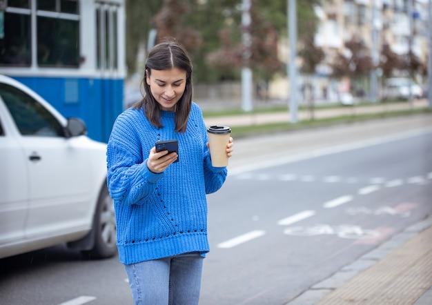 Straatfoto van een jonge vrouw met een telefoon in haar hand en een kopje koffie to go