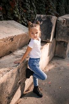 Straatfoto van een klein mooi meisje in jeans en een wit t-shirt op een achtergrond van betonnen platen en herfstbladeren