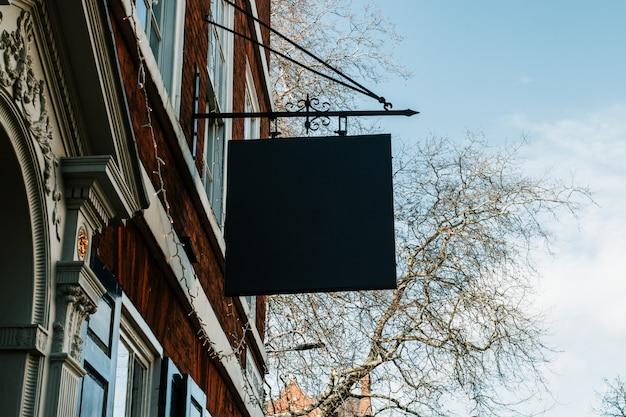 Straatlandschap van een zwart leeg teken dat van een gebouw hangt