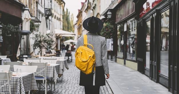 Straatmeisje in de stad toerist met rugzak is aan het rondkijken in de straten van ljubljana, slovenië
