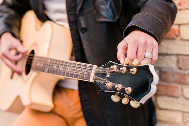 Straatmuzikant close-up gitaar stemmen vingers draaien aan de stemsleutels van een akoestische gitaar