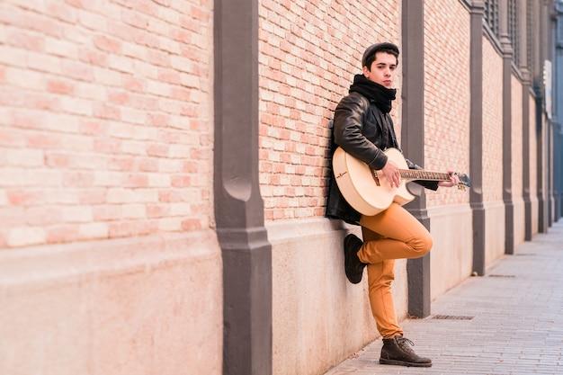 Straatmuzikant die akoestische gitaar speelt jonge knappe man met jas en hoed buitenshuis