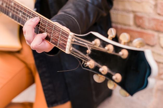 Straatmuzikant die gitaar speelt selectieve focus op de linkerhand gitaarhals close-up