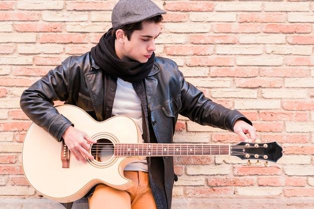 Straatmuzikant stemt de gitaar vingers draaien aan de stemsleutels van een akoestische gitaar
