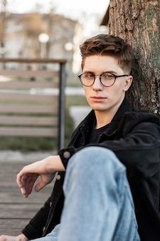 Straatportret amerikaanse jongeman met stijlvolle bril in modieuze denim