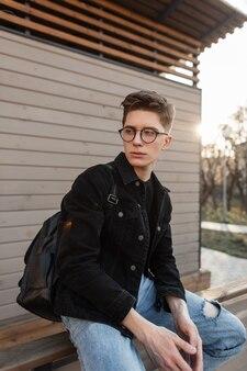 Straatportret amerikaanse jongeman met vintage bril in spijkerjasje met rugzak in de stad bij zonsondergang Premium Foto
