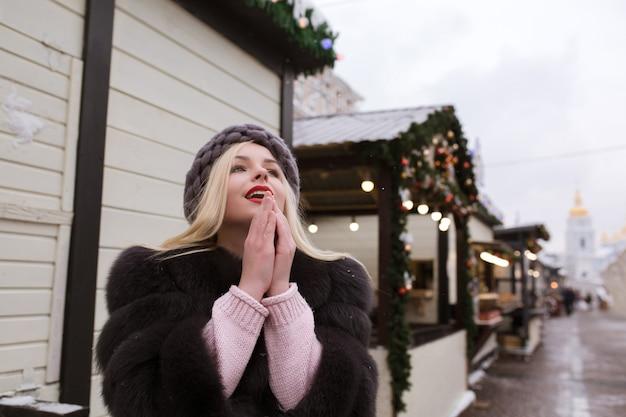 Straatportret van een aantrekkelijke jonge vrouw met een stijlvolle gebreide muts en bontjas, poserend op de kerstmarkt. ruimte voor tekst