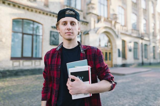 Straatportret van een jonge student in een shirt en boeken en notebooks in handen tegen de achtergrond van het lichaam van de universiteit. studentenleven.