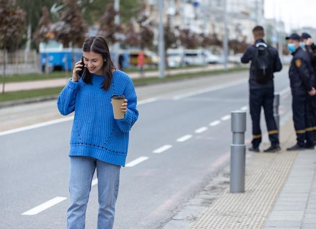 Straatportret van een jonge vrouw die aan de telefoon praat in de stad bij de rijbaan the