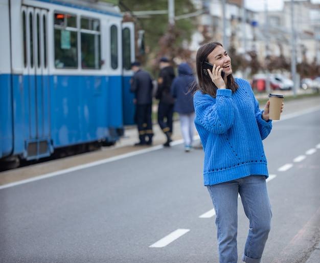 Straatportret van een jonge vrouw die aan de telefoon praat in de stad in de buurt van de rijbaan.