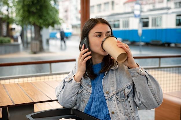 Straatportret van een jonge vrouw die koffie drinkt, telefoneert en op iemand wacht