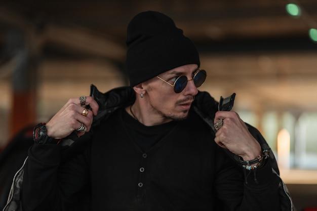 Straatportret van een knappe jongeman met een modieuze zonnebril in een stijlvolle zwarte jas met een hoed die door de stad loopt