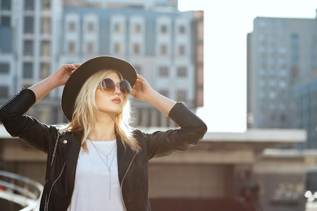 Straatportret van een prachtig blond meisje met een hoed en een vintage zonnebril. ruimte voor tekst