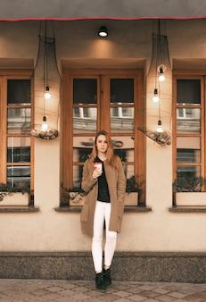 Straatportret van een stijlvol meisje in volle gang, het dragen van lentekleren, permanent met een kopje koffie in haar handen en op zoek naar de camera