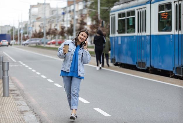 Straatportret van een vrolijke jonge vrouw die aan de telefoon praat met koffie aan haar hand.