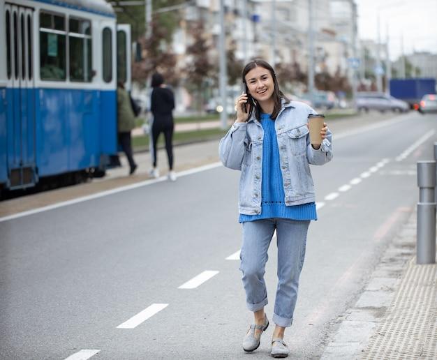 Straatportret van een vrolijke jonge vrouw die aan de telefoon praat met koffie aan haar hand