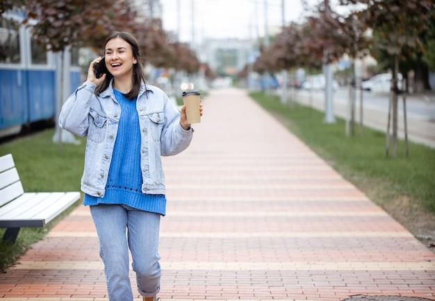 Straatportret van een vrolijke jonge vrouw die aan de telefoon praat met koffie naar haar hand kopieerruimte