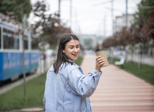 Straatportret van een vrolijke jonge vrouw op een wandeling met koffie op een wazige achtergrond