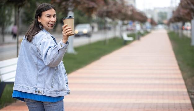 Straatportret van een vrolijke jonge vrouw op een wandeling met koffie op een wazige achtergrondkopieerruimte