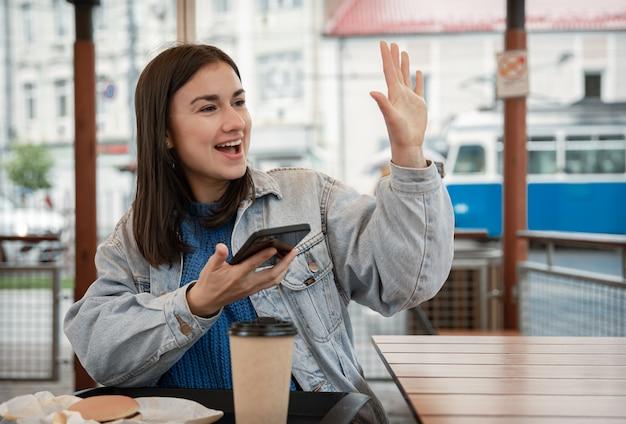 Straatportret van een vrolijke jonge vrouw op het terras van een café, die op iemand wacht