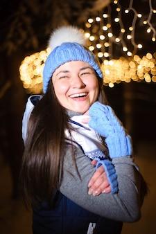 Straatportret van glimlachende mooie jonge vrouw op de feestelijke kerstmismarkt