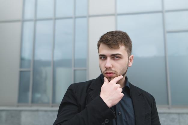 Straatportret van het knappe jonge zakenman stellen op grijze muur.