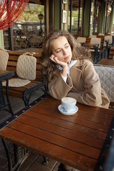 Straatportret van jonge vrouw die beige laag het drinken koffie op koffieveranda dragen met dromerige en nadenkende starende blik