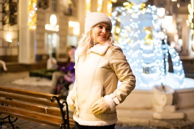 Straatportret van lachende mooie jonge vrouw op de feestelijke kerstmarkt. dame die klassieke stijlvolle wintergebreide kleding draagt.