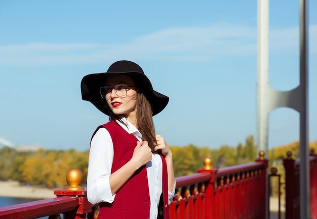 Straatportret van modieuze vrouw draagt rood kostuum, zwarte hoed en stijlvolle bril, poserend op een zonnige dag. ruimte voor tekst