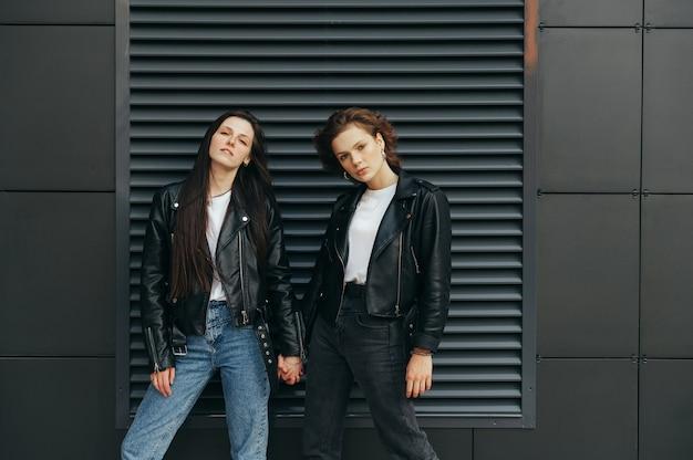 Straatportret van twee stijlvolle meisjes in leren jassen