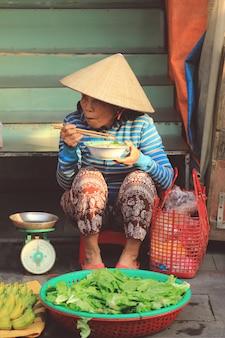 Straatverkopers die haar lunch in hanoi, vietnam hebben