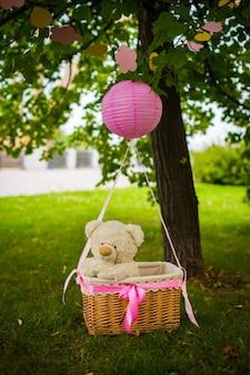 Straatversieringen voor een kinderfeestje. een mand met een teddybeer in een luchtballon in een groen park.