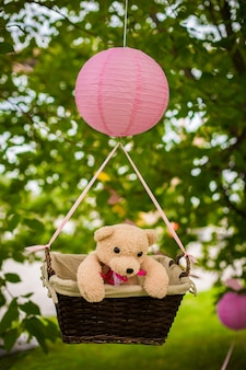 Straatversieringen voor een kinderfeestje. een mand met een teddybeer in luchtballon in een groen park