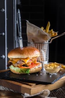 Straatvoedsel, fastfood, junkfood. zelfgemaakte sappige hamburger met rundvlees, kaas en spek met frietjes op de donkere en zwarte achtergrond