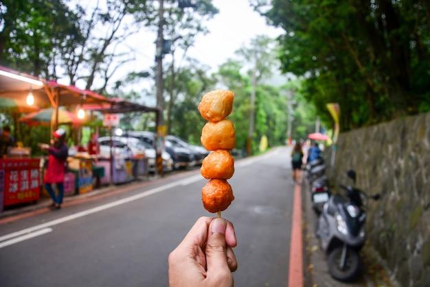 Straatvoedsel, hand die gefrituurde garnalenbal op de houten vleespen houden