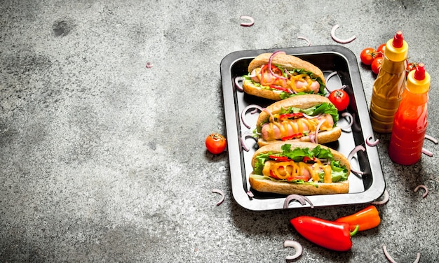 Straatvoedsel. hotdogs met kruiden en groenten in de pan op rustieke tafel.